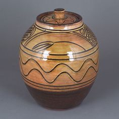 Michael Cardew : Jar, earthenware white slip with combed ear of wheat and linear design between a rich amber glaze.