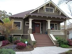 The picture is an example of a Craftsman home. This type of houses were originated entering this period.  These types of homes feature porches with overhanging roofs, tapered or square columns supporting the roof, a hand crafted look using wood and stone including inspiration from a famous American architect Frank Lloyd Wright.