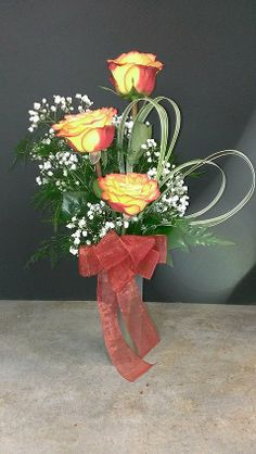 """Three Rose Bud Vase  Three """"High & Magic"""" Roses with a hand-formed lily grass heart."""