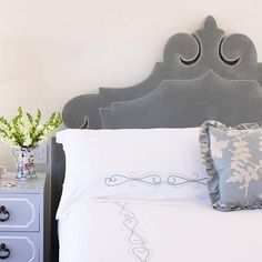 Carved in Style  The sculptural shape of this upholstered headboard mimics the look of carved wood, but it's much softer to lean against. The velvety blue upholstery picks up the flourishes on the bedding and throw pillow.