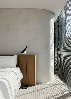 Quarto com parede curva, piso cinza, janelas do piso ao teto, cama com cabeceira de couro marrom, luminária de piso preta. Casa Minimalista em Melbourne  por Davidov Partners Architects
