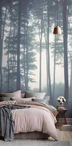 forest with gray misty trees, ambient photo wallpaper, near bed with pastel pink, and pale gray covers and cushions, large wall art, in room with high ceiling