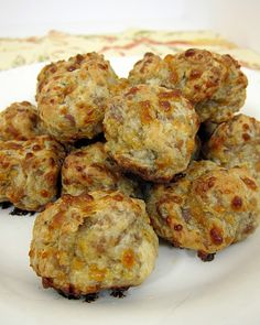 Sausage Balls The family loves this. So simple too.  1 Small (1 lb) box Bisquick  1 Package breakfast sausage  2 cups finely grated cheese  Mix together really well. no water needed. Form into balls place onto cookie sheets, bake at 350* for 12-15 minutes... ENJOY!