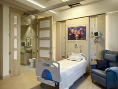 A wide bathroom door opening and patient lift ease patient transfers, while warm interiors downplay the institutional look of this bariatric hospital room. Photo: Larry Taylor, Photographer.