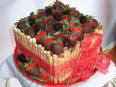 Beautiful cake topped with chocolate-covered strawberries & surrounded by Delicate rolled cookies.