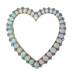 "Handmade antique heart shape brooch. Set with 36 oval graduating natural fire opals- flashes of blue, green and pinks.Edged with 35 rose cut diamonds. The pin measures an impressive 2"". Circa 1880s"