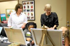 Sandy Coleman, a member of our Educational Support Services team overlooks artwork created by our recipients with Maggie Varney Founder & CEO.