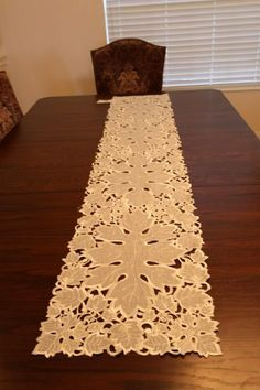 """Embroidery Cutout Table Runner, White Satin 13"""" X 72"""" by Decorating Touch. $27.60. Table Runner, Polyester. Add a touch of simply beautiful wildflowers to a dining table, buffet, or dresser. This finely crafted table runner is cut-out work so it makes a fresh-as-a-daisy setting for your summertime decorating and entertaining. Polyester; imported. Machine wash."""