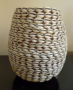 Antique woven basket covered with cowrie shells from the Yoruba tribe in Nigeria. It is known as a money basket, cowrie shells have been used as money. Handwoven natural fiber w/ cowrie shells and coins.