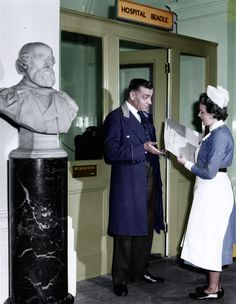 TheBeadle (Head Porter) Mr Streeton at St Thomas's Hospital been given a task by one of the nurses. This photograph was taken in 1960 when the Beadles were effectively the head porter of the hospital.
