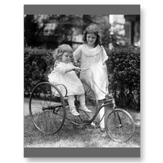 Old 1920s photo of two little girls in summer dresses, one on antique tricycle, 1922.
