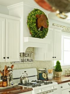 A custom range hood gives this country kitchen a high-end treatment. The marble herringbone backsplash and butcher block countertops add simple country style against the white cabinetry. An iron cow bust plays into the theme while a wreath around it's neck adds a splash of playful color.