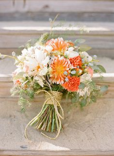 Coral, orange, and white bouquet tied with twine