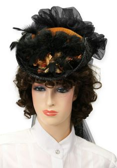 Small, jaunty outing hats enjoyed long popularity during the Victoria Era and were often worn by fashionable ladies on their morning walks. Our version features flowers, feather, lace and netting. Built on a black straw hat form for year round comfort, this hat will add a little pizzazz to your ensemble. Handmade in the USA so detailing of hat may vary slightly. One size fits most. Inside hat circumference measures approximately 21 inches. Hat also features an elastic strap to hold into…