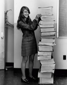 Lead software engineer of the Apollo Project Margaret Hamilton standing next to bound volumes of code handwritten by her and her MIT team that was used to take humanity to the moon. [1969]