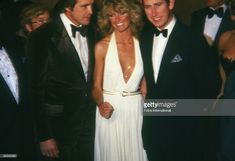 Portrait of married American actors Lee Majors (left) and Farrah Fawcett as they pose with British royal Prince Charles at a benefit in honor of the Prince's US visit, Beverly Hills, Callifornia, late October 1977.