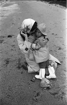 Jacqueline Kennedy comforts daughter Caroline Kennedy on a rainy day at the beach in Hyannis Port, Massachusetts, circa 1960.
