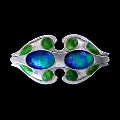 This is not contemporary - image from a gallery of vintage and/or antique objects. MURRLE BENNETT & Co. (1896-1914) for LIBERTY & Co.  A silver brooch enamelled with tones of blue and green.   Anglo/German c.1900. Marks for MB & Co. and marked 'SILVER'.   Size: Height 2.2 cm. Width 4.2 cm. (Fitted case)  Lit.: Liberty Style. Academy Editions. Illustrated page 74. J.4.