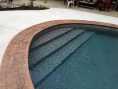 Vinyl liner w/ vinyl over steps and stamped & stained concrete coping.  by Aqua Fun.