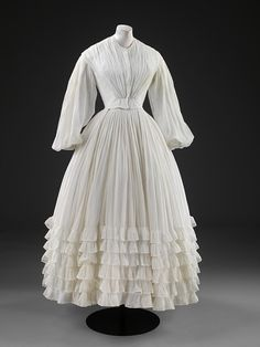 Wedding dress and petticoat, Britain, c 1851. Cotton muslin lined with linen, sleeves trimmed with bobbin lace. Victoria & Albert Museum.