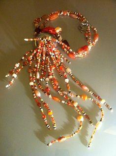 Une cascade de cornalines d'agates, de perles de coquillages et de corne jaillissent d'un élément en métal argenté. ANEHO Création  a-neho.com Agates, Christmas Bulbs, Creations, Holiday Decor, Jewelry, Home Decor, Carnelian, Sea Shells, Beads