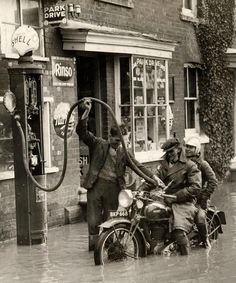 England 1935 - A gas station attendant fills the tank on a motorcycle carrying two people during a small flood. Everyone seems so chipper. Motos Retro, Motos Vintage, Vintage Bikes, Vintage Motorcycles, Vintage Cars, Retro Bikes, Honda Motorcycles, Vintage Iron, Vintage Travel