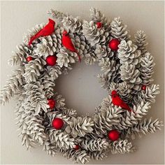 Pinecone Wreath with Cardinals and Ornaments--This pinecone wreath will sparkle and pop with color after a few simple additions. To make, coat a store-bought pinecone wreath with gray spray paint. Spray with spray snow, then silver glitter, allowing drying time between coats. Arrange three cardinal figurines and nine round red ornaments among the pinecones, adhering with hot glue to keep them in place.