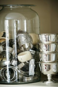 collection of silver napkin rings, set of hotel silver bowls, large blown glass jar by dollie