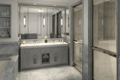 Gray bathroom boasts gray double vanity topped with white marble under frameless mirror illuminated by long sconces atop gray marble tiled floor flanked by gray marble clad drop-in tub placed under built-in shelves tiled in gray marble to the left and  chrome doors leading into his and her showers to the right.