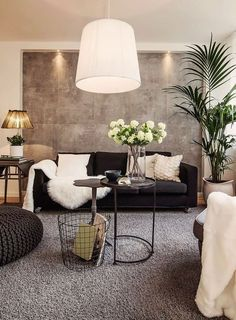 Sala de estar com tapete cinza, sofá preto, pelego decorativo branco, almofadas brancas. Parede com placas cinza. Dicas e Inspirações de Mantas para Sofá