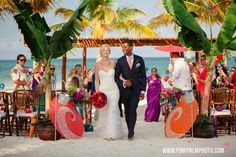 Tropical inspired wedding design with bright colorful florals in red purple and oranges with colorful paper umbrellas for this beach Indian wedding. #mishkadesignsmexico #secretsmaroma
