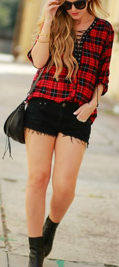 An edgy fall transition outfit styled with a lace up plaid top, distressed black jean shorts, black ankle booties, and Valley Eyewear sunglasses