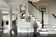 Foyer with dark wood floors, animal print stair runner, and off-white walls with white trim  | Jennifer Pacca Interiors