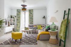 Salón diseñado por Natalia Zubizarreta Interiorismo en la reforma integral de vivienda en Bilbao, Vizcaya. Sofá beige de Fama, mesilla mimbre, centro puff, alfombra, lámpara de pie, muebles de TV y cortinas de Ikea. Paviemento laminado acabado roble aserrado blanqueado, escalera verde, mantas y complementos decorativos de Zara Home, lámpara hecha con damajuana, lámpara techo hecha a medida con pantallas diferentes de mimbre.