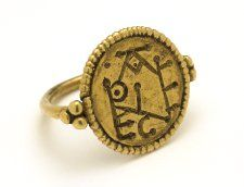 Gold finger-ring; bezel an applied disc; incised monogram; beaded wire border; three pellets on shoulders; hoop a rod; terminating under bezel in flat heart-shaped scrolls.