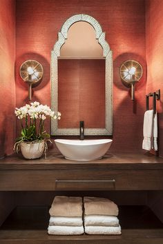 Pink walls, fresh flowers, and a wooden vanity give this small bathroom a feminine, contemporary style.