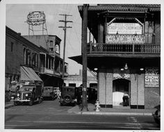 """man crouching outside the door to Tuey Farlow Cafe, ca. 1937 