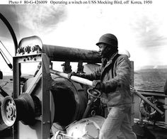 Korean War Minesweeping    Crewman operates a winch on board USS Mockingbird (AMS-27) during mine clearance operations off Wonsan, North Korea. The ship's name is seen on a lifering mounted on the bulwark in the lower right. Original photo is dated 14 November 1950.    Official U.S. Navy Photograph, National Archives.    NOTE: This image appears to be a double exposure, producing minor disfigurement, mainly at the right.