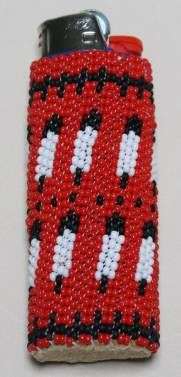 Feather Lighter Case The lighter case is a circular weave of seed beads forming a feather design. The case fits a disposable lighter. When the lighter is empty, slide lighter out and replace with a new lighter. Available in blue, green, purple, and red. Made by E. Descheny (Navajo)
