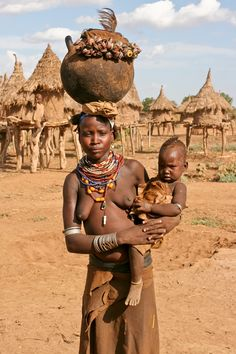 Africa | A Dassanech mother and child standing in front of the granary. | © Frans Devriese