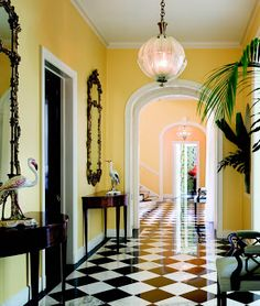 Entryway with checkerboard marble tile and Venetian sconces in the Lauder Palm Beach mansion