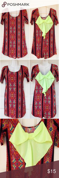🆕 Back Bow Boho Hippy Tunic Dress NWOT! New without tags! This is a beautiful short dress with short sleeves. It has a unique mosaic geometric pattern in orange, red, yellow, pink, blue, and black. The back has a gorgeous bow in neon green, making it a showstopper piece. It's trendy and has a boho vibe. Can also be worn as a great tunic top with leggings for the taller ladies. NO swaps/trades!  92% Polyester, 8% Spandex. Made in the USA!   Approximate measurements: Length: 31 inches Bust…
