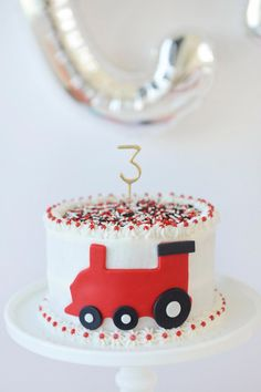 Red, white, and black train birthday cake with gold cake topper candle. Red, white, and black train birthday cake with gold cake topper candle. Choo Choo Party styling by Red Birthday Cakes, Toddler Birthday Cakes, Novelty Birthday Cakes, Trains Birthday Party, Happy Birthday, Birthday Cupcakes, 2nd Birthday, Birthday Ideas, Lightning Mcqueen Birthday Cake