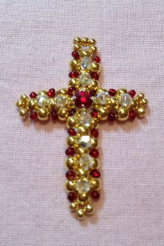 Right Angle Weave Christmas Cross. Bead seven boxes down and five across. Decorate top with Swarovski crystals and red montee. Designed and handcrafted by Pam Keith