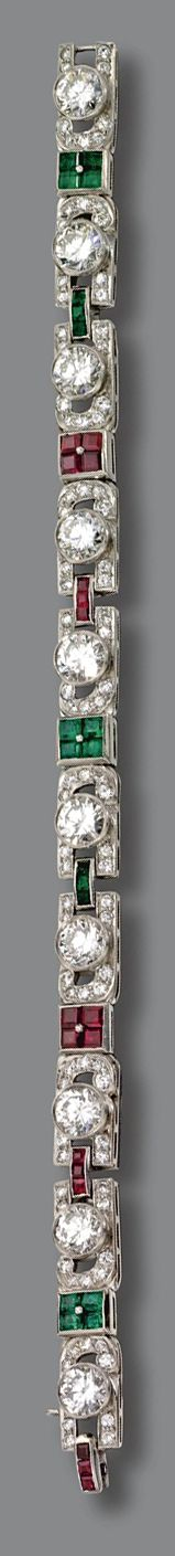 DIAMOND, RUBY AND EMERALD BRACELET, CIRCA 1930.  Set with 10 round diamonds weighing approximately 9.25 carats, bordered by 90 round, old European-cut and old mine-cut diamonds weighing approximately 1.80 carats, connected by alternating calibré-cut rubies and emeralds, mounted in platinum, length 7 1/8 inches.