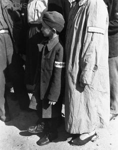 A six-year-old war orphan, with a Buchenwald badge on his sleeve, waits for his name to be called during roll call at Buchenwald camp, Germany, for departure to a new life in Switzerland at the end of World War II