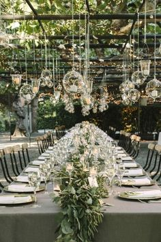 Create a stunning tablescape by hanging glass candle holders above a long floral table.