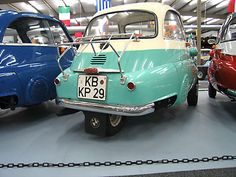 """1959 BMW Isetta 300 3-wheel special. When casually looking at the average BMW Isetta, it would appear to have only a single wheel at the rear, but in fact there were Two wheels at the rear in the standard configuration, they were just spaced closer together. Sometimes altered to suit certain markets as Switzerland, where a PAIR of wheels were stuck next to each other. This allowed for better stability and traction, but still allowed the car to be classified as a """"3 wheeled vehicle""""."""