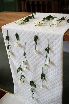 witte rozen als decoratie op wit tafelkleed