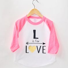 L is for LOVE will be applied to a 3/4 Sleeve Pink and White or Black and white Raglan Tee from American Apparel. These baseball tees are a super soft, light weight poly/cotton blend.